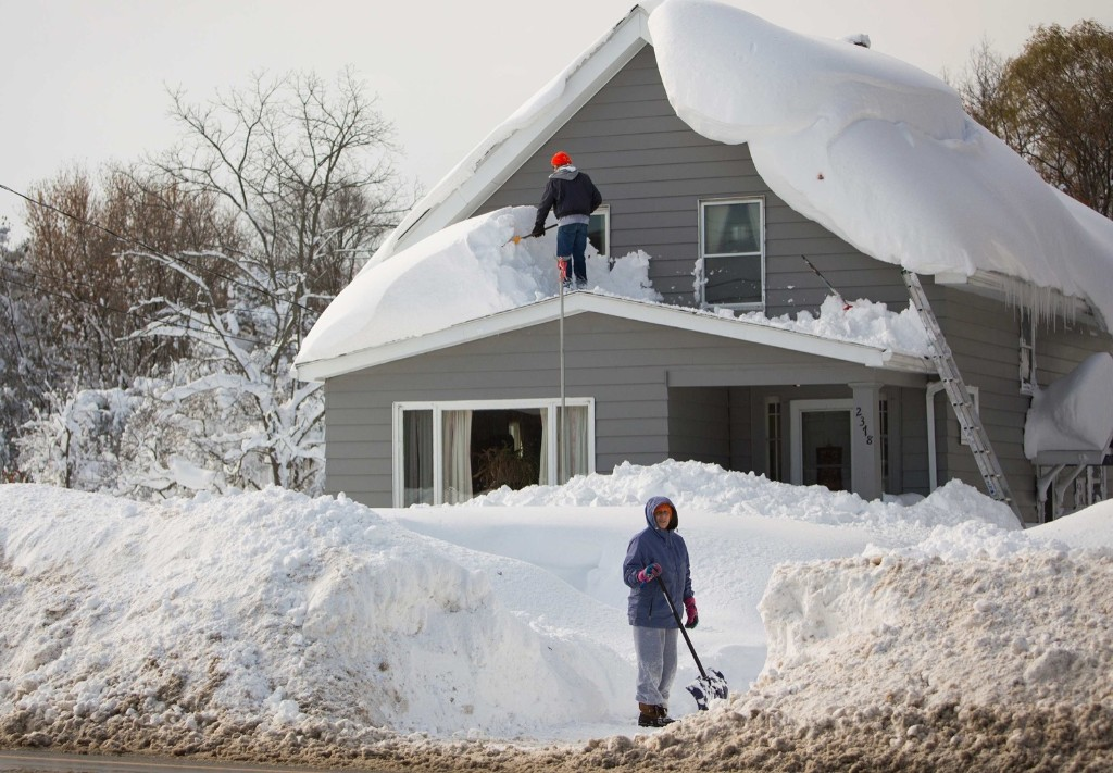 A man clears snow from his roof in the town of Cheektowaga near Buffalo, Wednesday. REUTERS/Lindsay DeDario