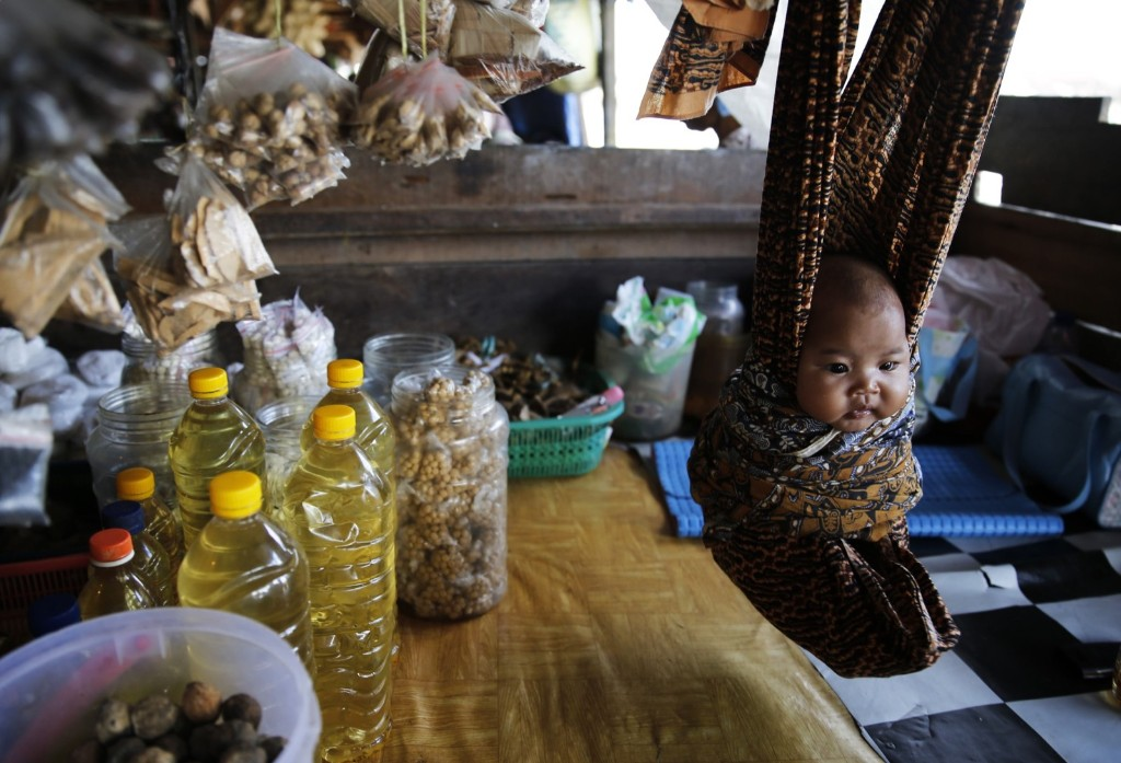 A baby in a cloth hammock at a food stall at Sungai Arut market in Pangkalan Bun, Indonesia. REUTERS/Beawiharta