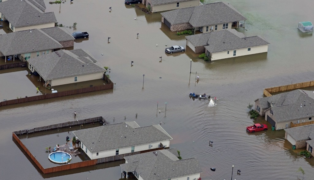 A boat motors between flooded homes in Hammond, La., Saturday. AP Photo/Max Becherer