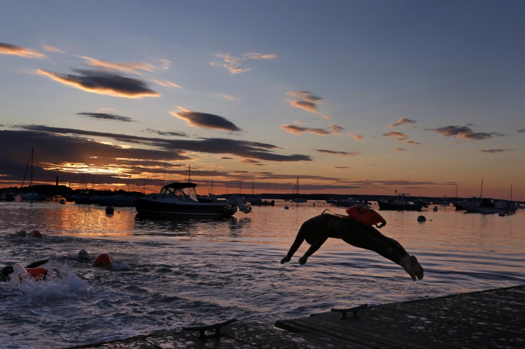 A long-distance swimmer dives into the Atlantic Ocean at dawn in Falmouth, Maine. AP Photo/Robert F. Bukaty