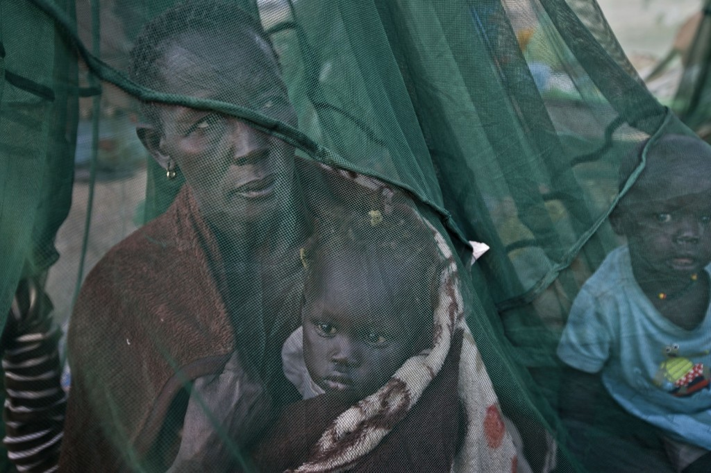 One of the few to have a mosquito net, a displaced family who fled the recent fighting between government and rebel forces in Bor, waking up in the town of Awerial, South Sudan, Thursday. AP Photo/Ben Curtis