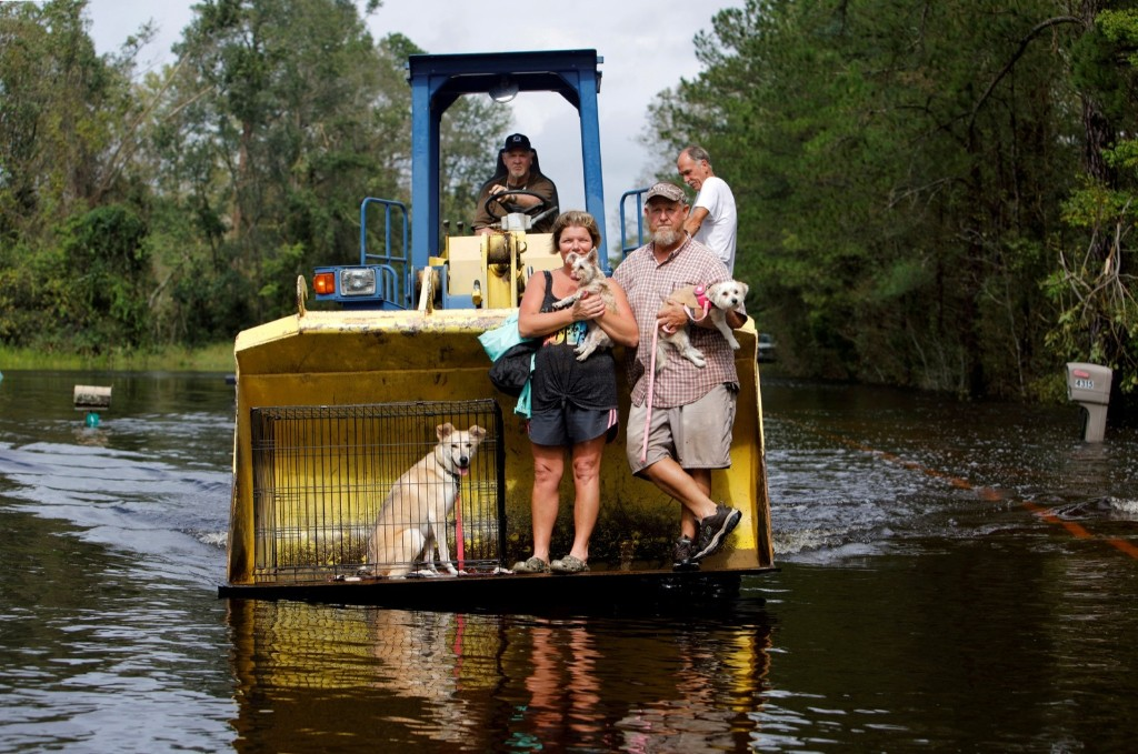 Jimmy Shackleford transports his son Jim and his wife Lisa, and their pets Izzy, Bella and Nala in the bucket of his tractor as the Northeast Cape Fear River breaks its banks during flooding after Hurricane Florence in Burgaw, N.C. REUTERS/Jonathan Drake