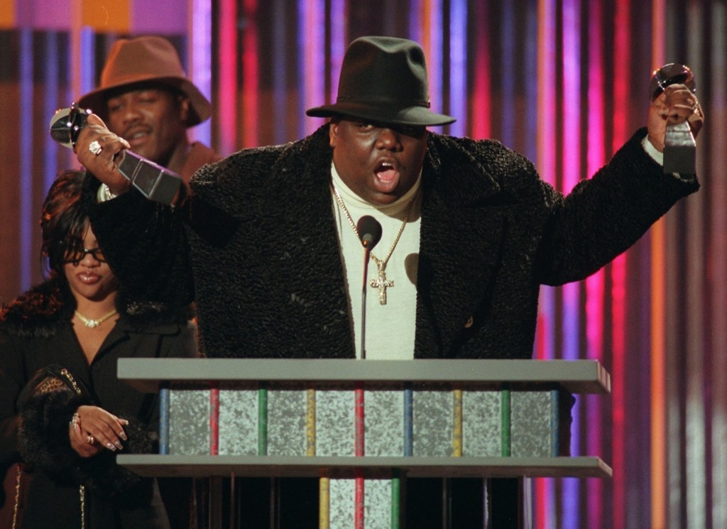 The Notorious B.I.G., who won rap artist and rap single of the year, clutches his awards at the podium during the annual Billboard Music Awards in New York, Dec. 6, 1995. AP Photo/Mark Lennihan