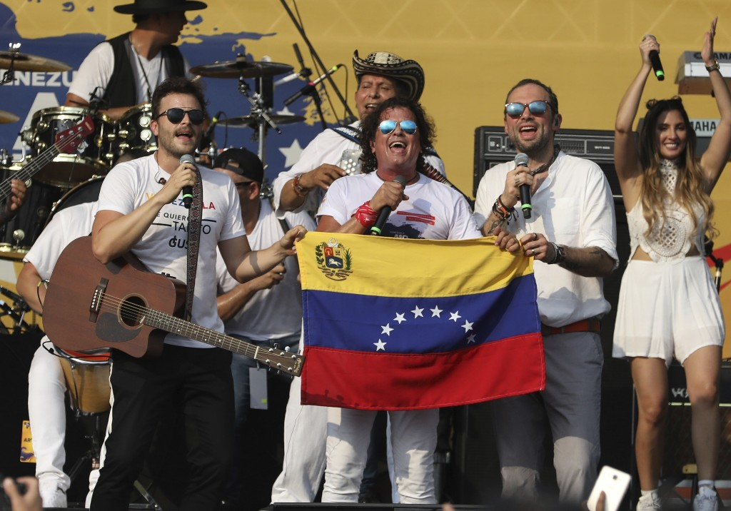 """Gusi, from left, Carlos Vives and Santiago Cruz, hold a Venezuelan national flag as they perform at the """"Live Aid Venezuela"""" concert at the Tienditas International Bridge on the outskirts of Cucuta, Colombia, Friday, Feb. 22, 2019, on the border with Venezuela. British billionaire Richard Branson organized the mega concert, which features dozens of Latin musicians performing on a giant stage on one side of what Colombian authorities have renamed the """"Unity"""" bridge. (AP Photo/Fernando Vergara)"""