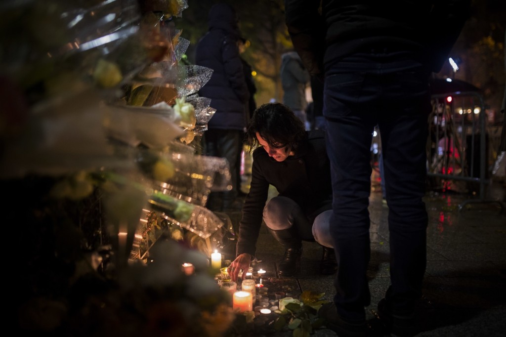 A woman lights a candle outside the Bataclan concert hall in Paris. AP Photo/Kamil Zihnioglu
