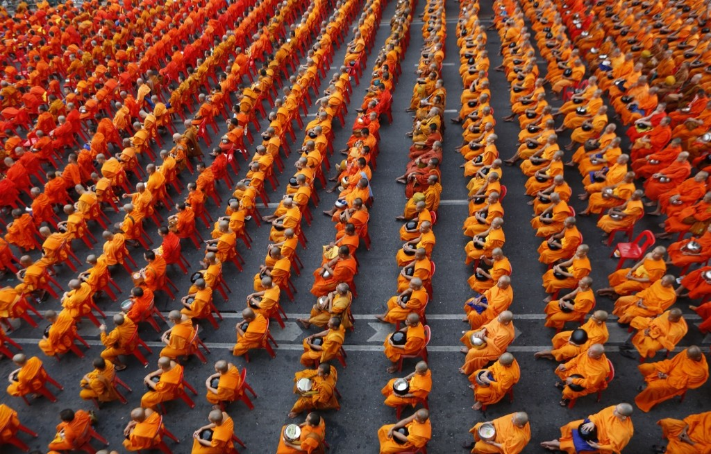 Buddhist monks holding bowls sit on chairs before civilians drop dried food into the bowls in Bangkok. AP Photo/Sakchai Lalit