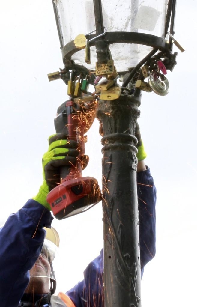 A Paris city employee uses a grinder to cut locks from a street lamp on the famed Pont des Arts bridge in Paris, Monday.AP Photo/Remy de la Mauviniere