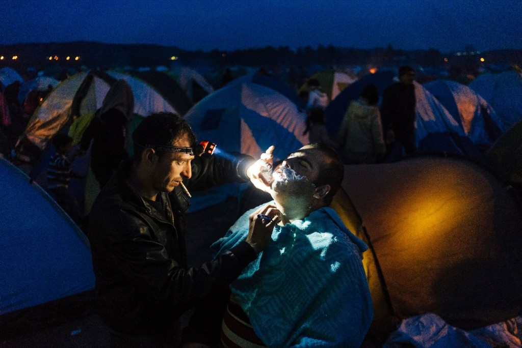 A Syrian barber shaves the beard of a customer in a migrant and refugee makeshift camp installed close to Greek-Macedonian border. DIMITAR DILKOFF/AFP/Getty Images