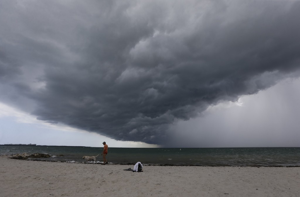 Arnie Powell walks along the beach with his pet dog, Biscuit, as rain clouds approach Hobie Beach in Key Biscayne, Fla. AP Photo/Alan Diaz