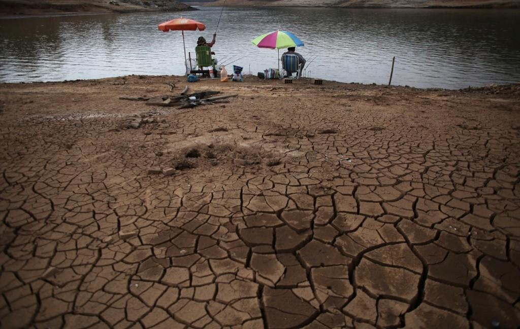 Men fish next to cracked ground as the Atibainha dam lake dries up in Nazare Paulista near Sao Paulo. REUTERS/Nacho Doce