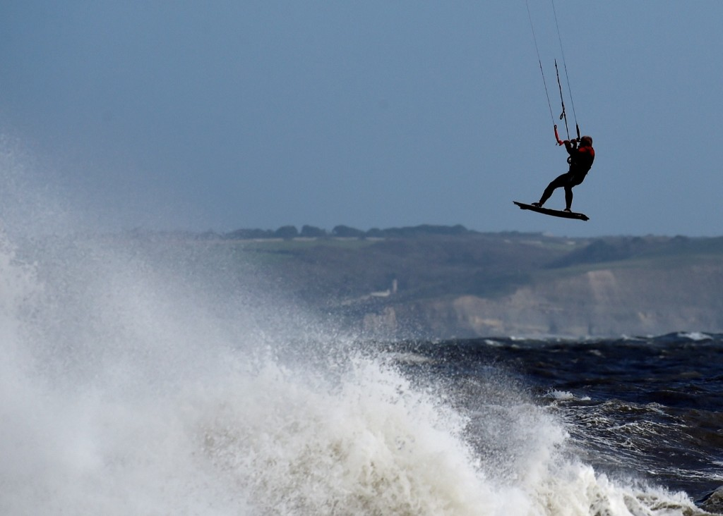 A kite surfer takes flight near the lighthouse as storm Ophelia passes Porthcawl, Wales. REUTERS/Rebecca Naden