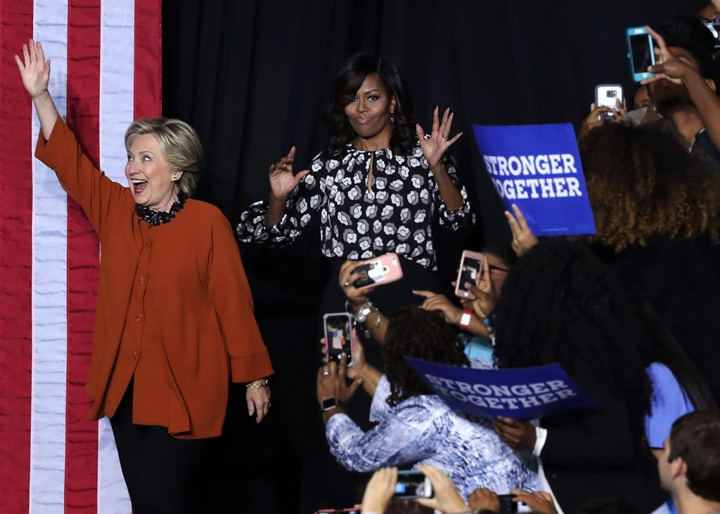 Hillary Clinton and First Lady Michelle Obama greet supporters during a campaign event at the Lawrence Joel Veterans Memorial Coliseum in Winston-Salem, N.C. Alex Wong/Getty Images