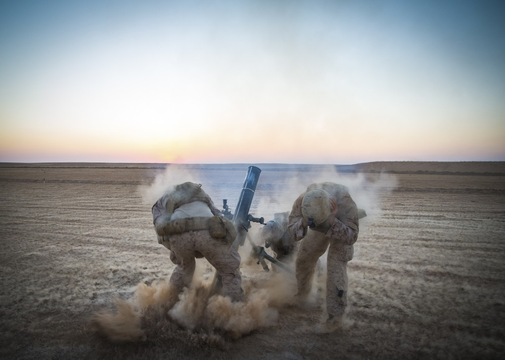 In this Sept. 10, 2018, photo released by the U.S. Marines, Marines with Weapons Company, 3rd Battalion, 7th Marine Regiment, fire mortars from an undisclosed location in Syria. The United States' main ally in Syria on Thursday, Dec. 20, 2018, rejected President Donald Trump's claim that Islamic State militants have been defeated and warned that the withdrawal of American troops would lead to a resurgence of the extremist group. (U.S. Marine Corps photo by Cpl. Gabino Perez via AP)