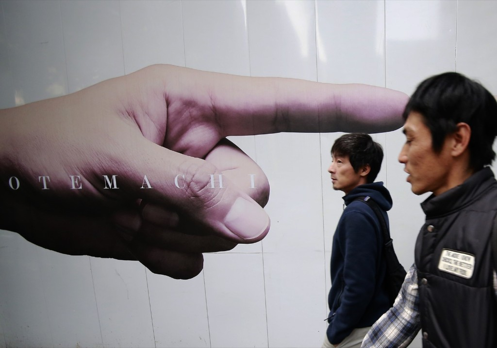 Men pass advertisements posted on the fence of a construction site in Tokyo's Otemachi business district. AP Photo/Shizuo Kambayashi
