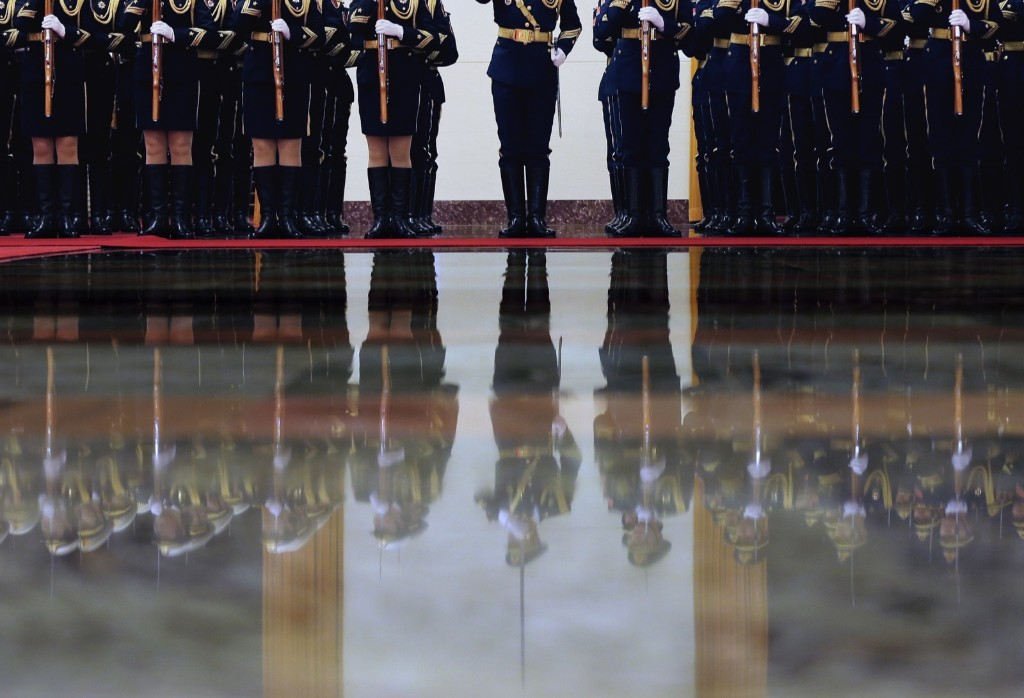 Chinese guard of honor are reflected as they rehearse for a welcome ceremony for visiting Thailand Prime Minister Prayuth Chan-ocha at the Great Hall of the People in Beijing. AP Photo/Andy Wong