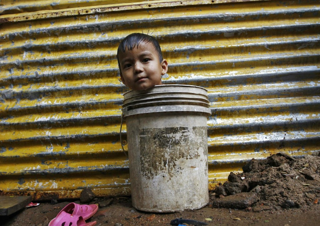A boy sits in a bucket while waiting for his mother to fetch water from a nearby hand pump to bathe him, outside a makeshift hut in the southern Indian city of Chennai, Monday. REUTERS/Babu
