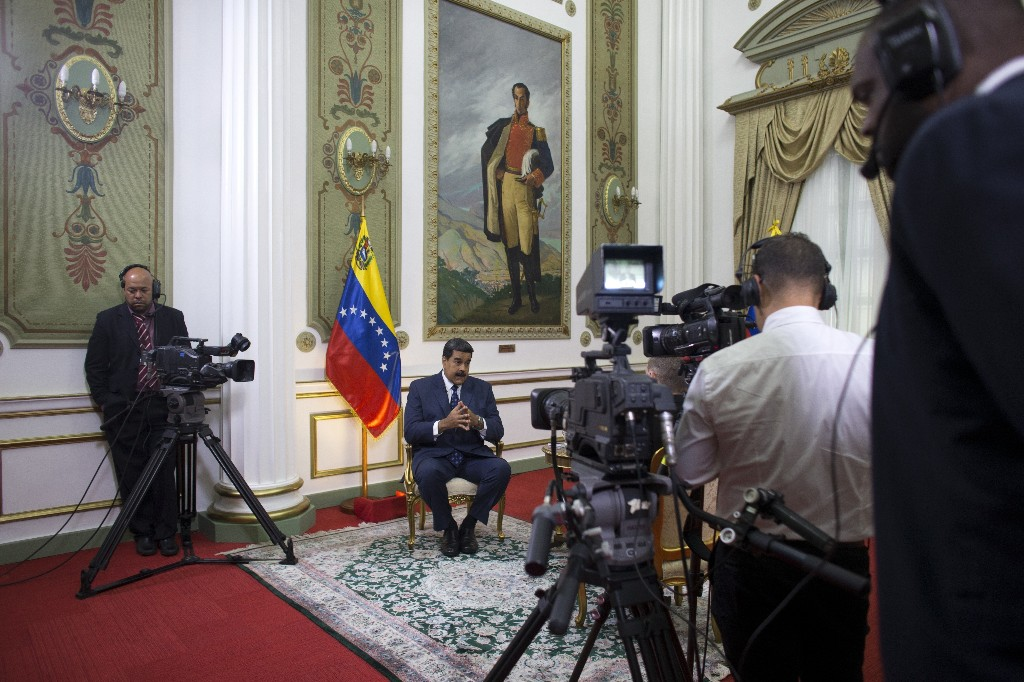 Venezuela's President Nicolas Maduro speaks during an interview with The Associated Press at Miraflores presidential palace, where a painting of independence hero Simon Bolivar hangs, in Caracas, Venezuela, Thursday, Feb. 14, 2019. Maduro is inviting a U.S. special envoy to come to Venezuela after revealing during the interview that his foreign minister recently held secret meetings with the U.S. official in New York. (AP Photo/Ariana Cubillos)