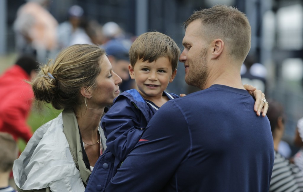 New England Patriots quarterback Tom Brady and his wife Gisele Bundchen with their son Benjamin Brady after a joint workout with the Tampa Bay Buccaneers at NFL football training camp, in Foxborough, August 13, 2013. AP Photo/Charles Krupa