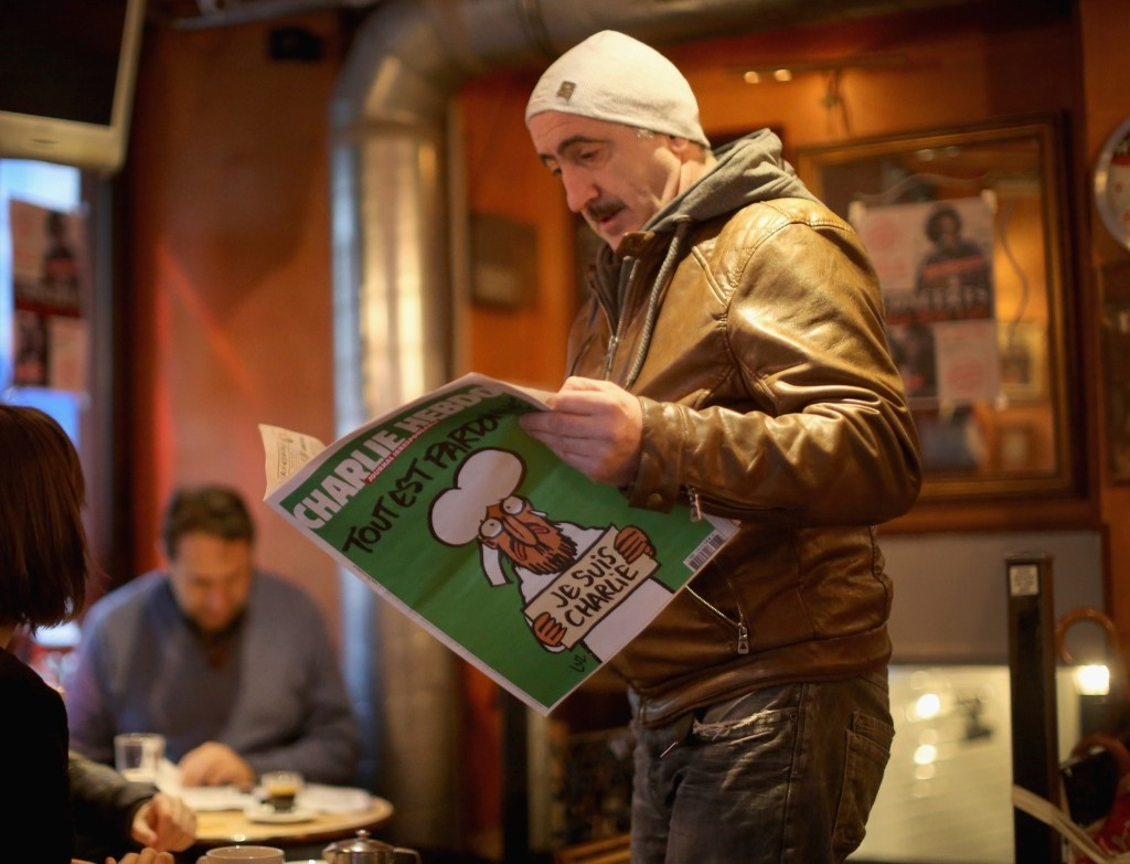 A man reads the the latest edition of Charlie Hebdo in a cafe, Wednesday in Paris. Christopher Furlong/Getty Images