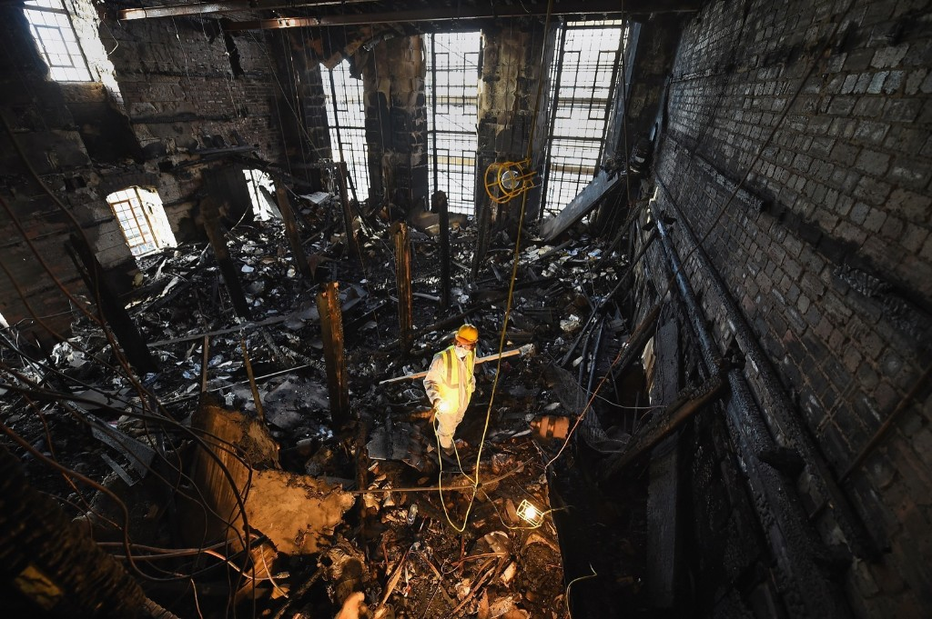 Forensic archaeologist Owen Godbert sifting through the ashes of a fire that damaged Mackintosh Library at the Glasgow School of Art. Jeff J Mitchell/Getty Images