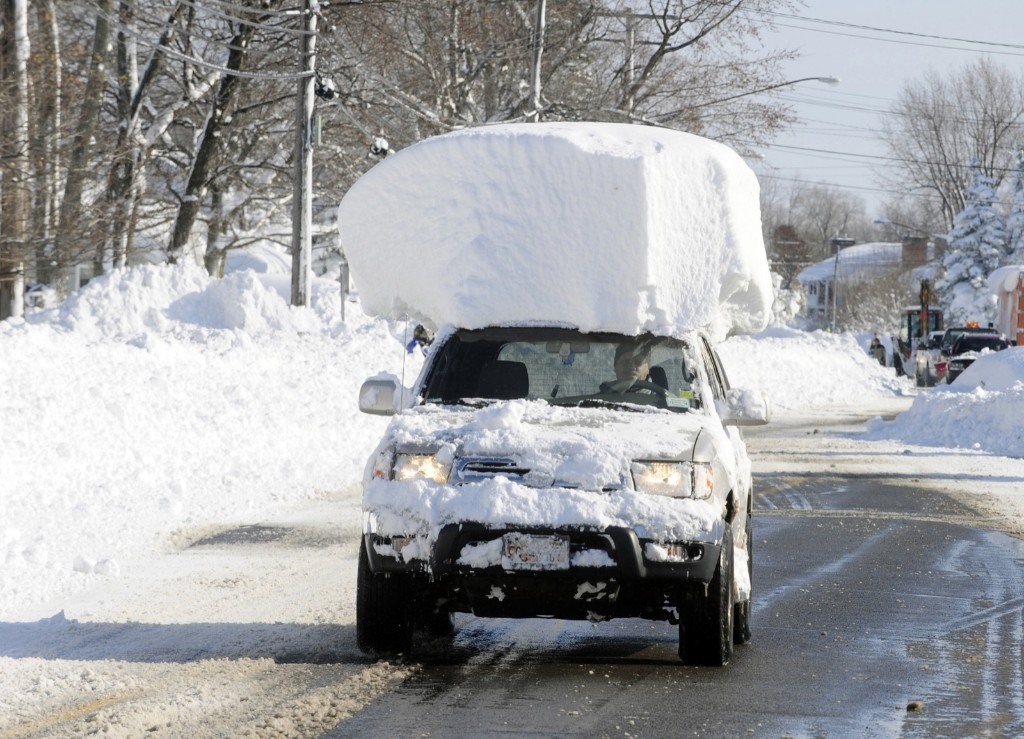A vehicle drives along Route 20 Wednesday after digging out of a massive snow fall in Lancaster, New York. The record setting lake effect snowstorm dumped up to six feet of snow in less than 24 hours on the Buffalo area. AP Photo/Gary Wiepert