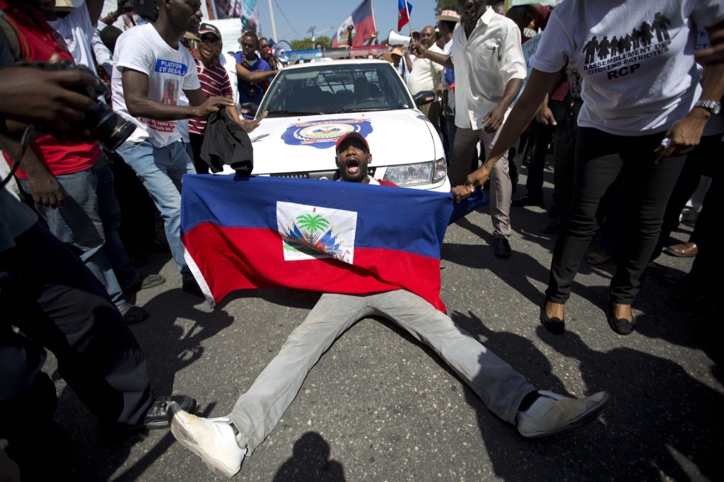 "A demonstrator holding a Haitian flag shouts, ""No racism"" as he blocks a police car during a march to protest the Dominican Republic's deportation of Haitians, in Port-au-Prince. AP Photo/Dieu Nalio Chery"