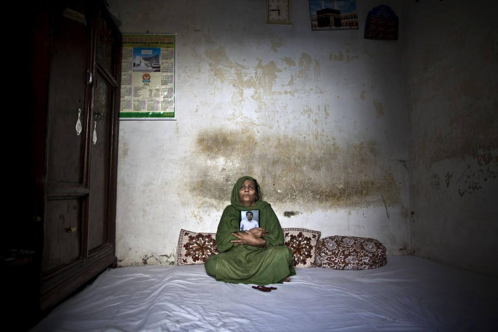 Pakistani Salima Akhtar, mother of Akmal Omar, who was killed by suicide bombers on March 3, grieves while embracing his photograph in his bedroom in Rawalpindi. AP Photo/Muhammed Muheisen