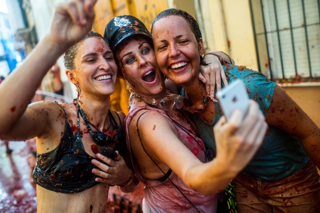 Revellers take a selfie as they enjoy the atmosphere in tomato pulp while participating the annual Tomatina festival, Wednesday, in Bunol, Spain. David Ramos/Getty Images