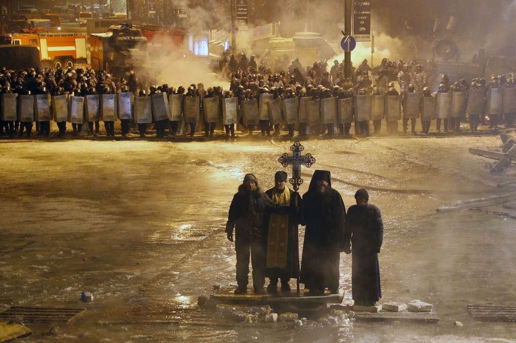 Orthodox priests pray as they stand between pro-European Union activists and police lines in Kiev, Jan. 24. AP Photo/Sergei Grits