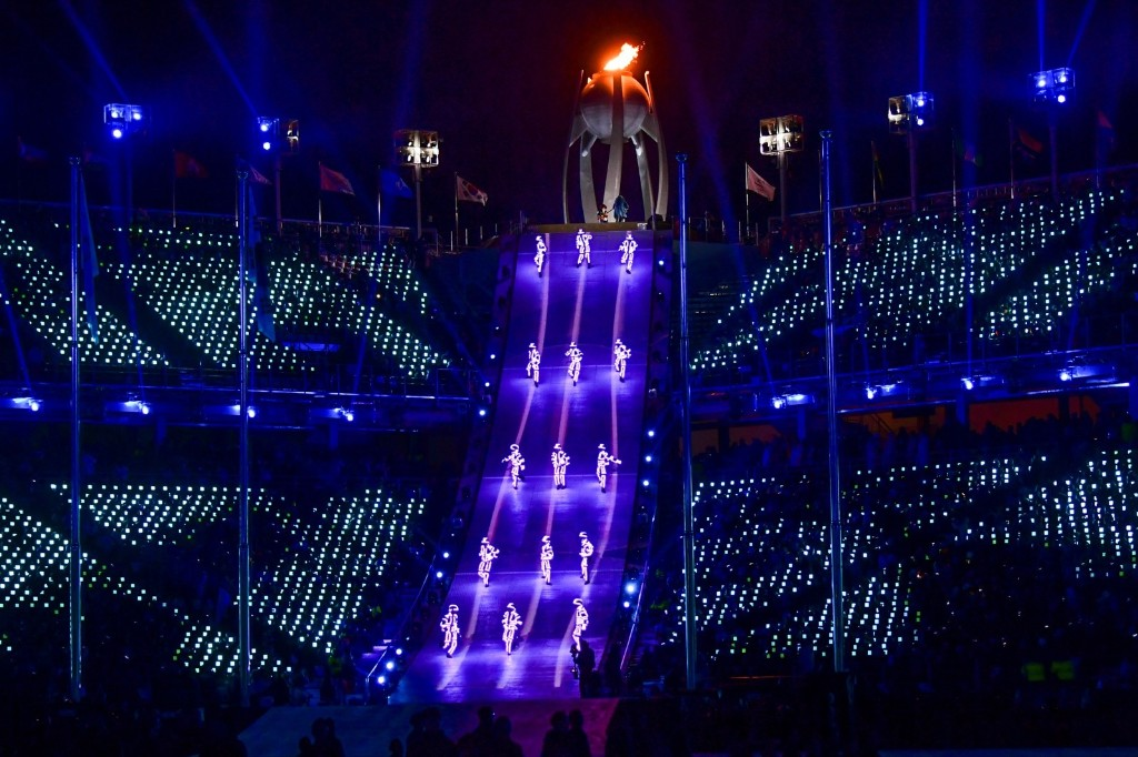 Artists perform near the Olympic flame during the closing ceremony. MARTIN BERNETTI/AFP/Getty Images