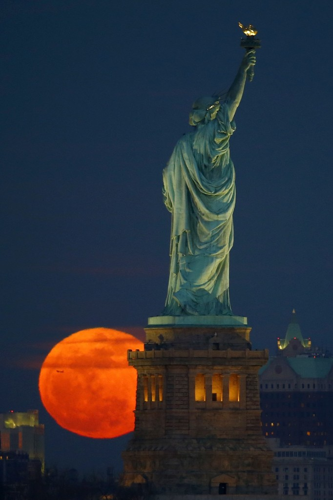 Full moon rising behind the Statue of Liberty. AP Photo/Julio Cortez