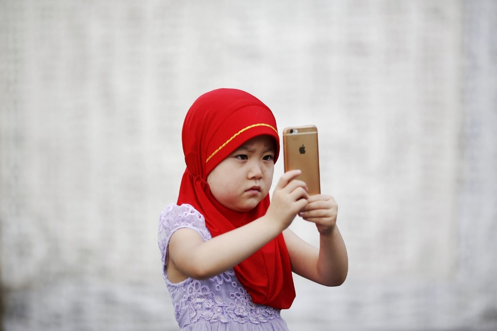 A girl takes pictures at the historic Niujie mosque as Muslims gather to celebrate the Eid al-Fitr in Beijing. REUTERS/Damir Sagolj