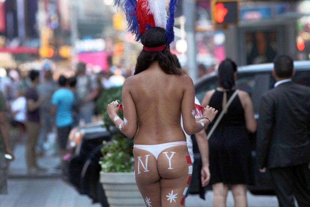A model in Times Square. New York Mayor Bill de Blasio has announced that the city is preparing to address the issue of topless and painted women who pose for pictures in Times Square while soliciting tips. Spencer Platt/Getty Images