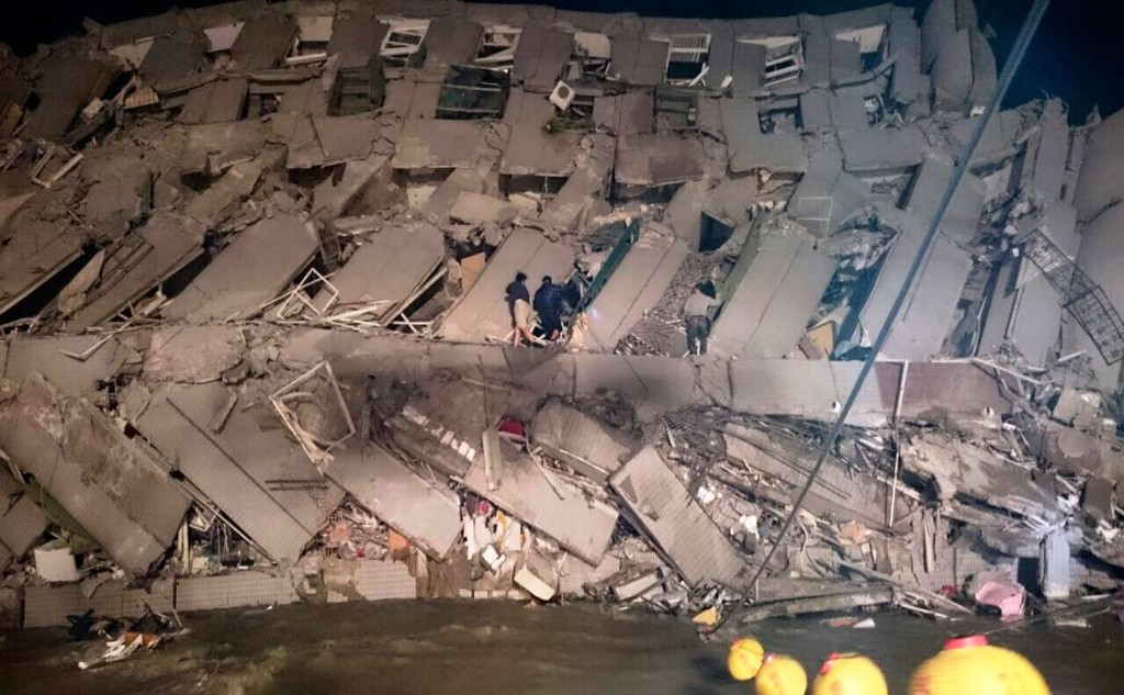 Rescuers try to enter an office building that collapsed on its side after an early morning earthquake in Tainan, southern Taiwan, Saturday. AP Photo