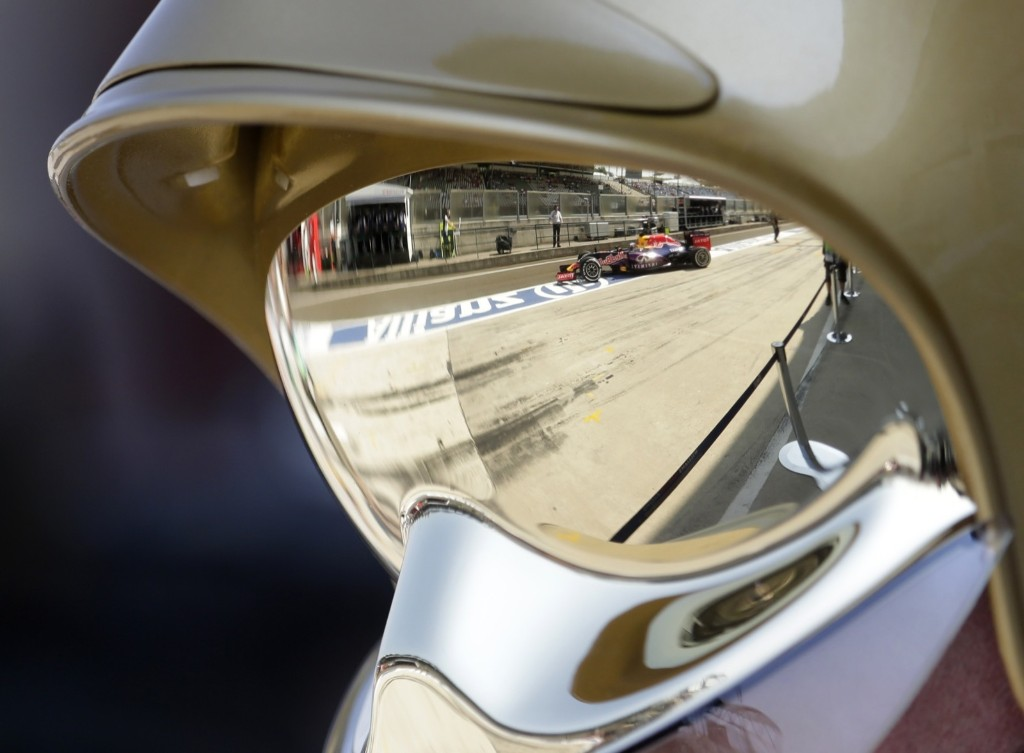 Daniel Ricciardo of Australia is reflected in a helmet of a track marshal during practice at the Hungarian Formula One Grand Prix in Budapest. AP Photo/Petr David Josek