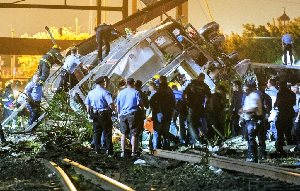 Rescue workers climb into the wreckage of a crashed Amtrak train in Philadelphia. REUTERS/Bryan Woolston