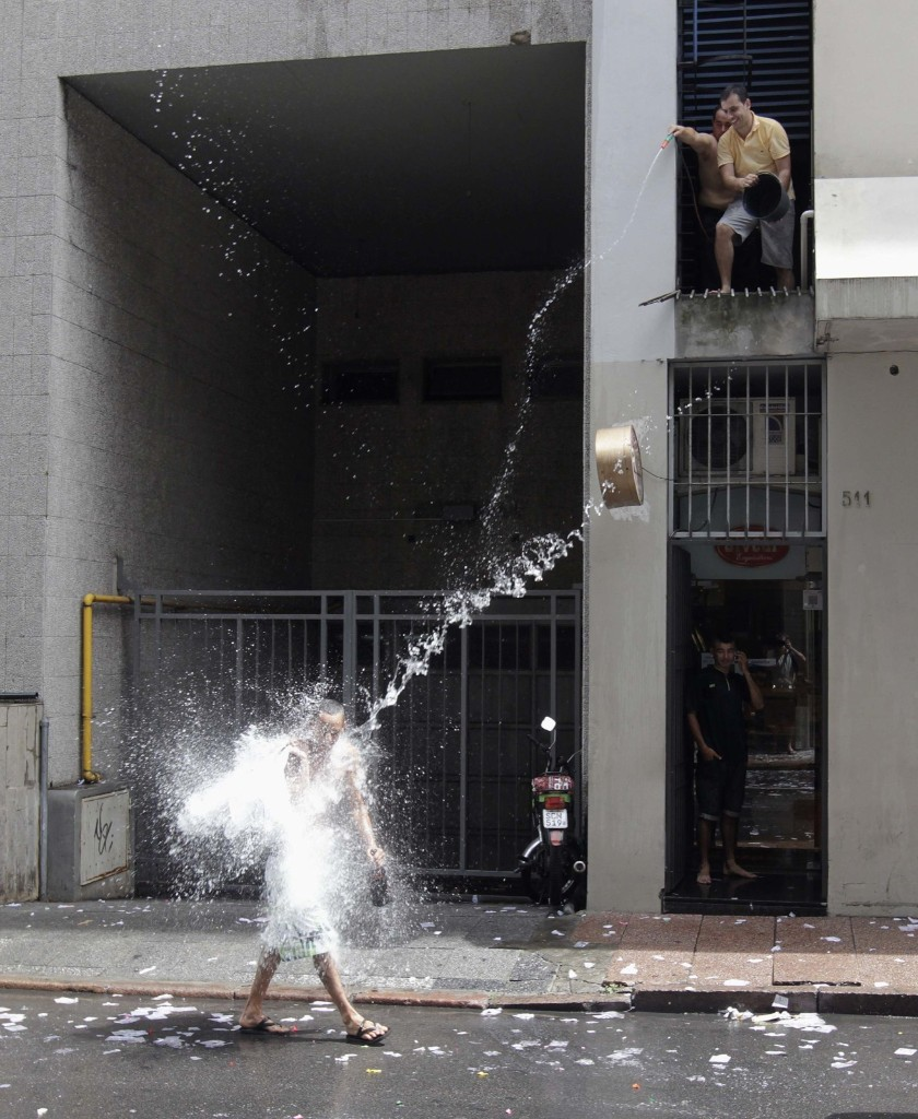 People in the Montevideo financial district throw water at unsuspecting passersby to mark the last working day of the year. REUTERS/Andres Stapff