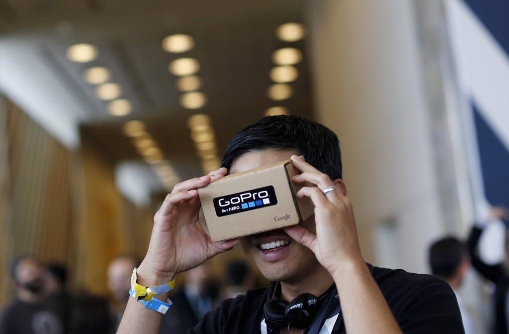 """A conference attendee looks through """"Google Cardboard,"""" a viewer that enables the user to view content from a smart phone in VR, during the Google I/O developers conference in San Francisco, Thursday. REUTERS/Robert Galbraith"""