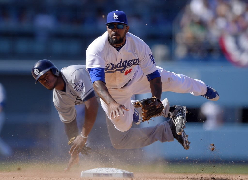 San Diego Padres' Justin Upton, left, is forced out at second as Los Angeles Dodgers second baseman Howie Kendrick throws out Will Middlebrooks at first during eighth inning of opening day in Los Angeles. AP Photo/Mark J. Terrill