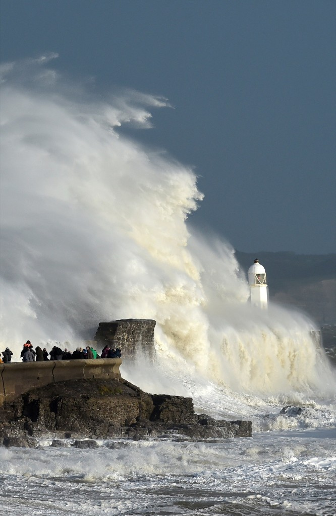 Waves crash over the lighthouse as storm Ophelia passes Porthcawl, Wales. REUTERS/Rebecca Naden