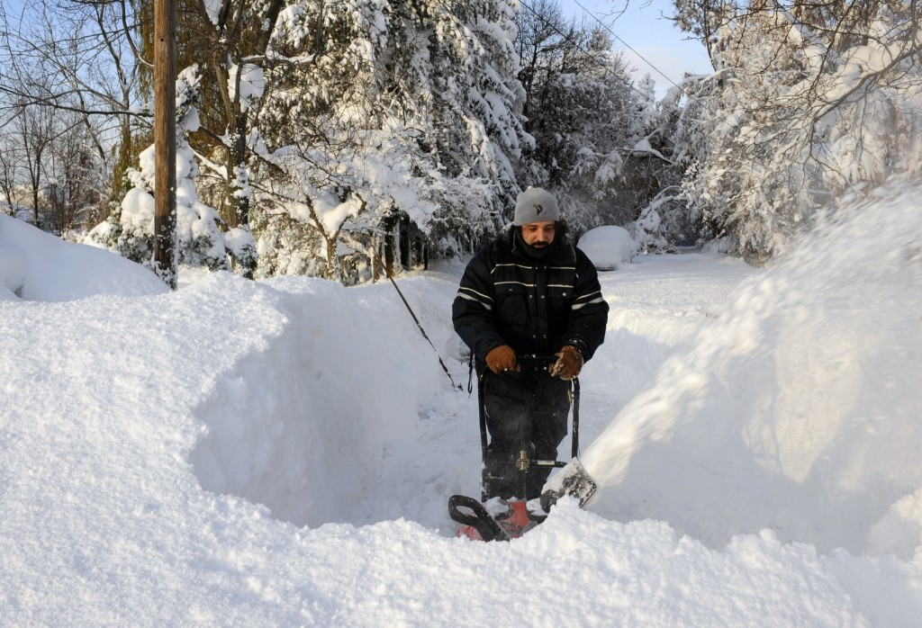 Bob Wilcox clears the snow at the end of his driveway on Bowen Rd. in Lancaster, New York, Wednesday. AP photo/Gary Wiepert