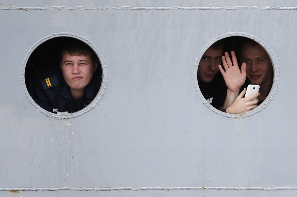 Russian sailors look through the portholes of the Russian Navy frigate Smolny as they leave the STX Les Chantiers de l'Atlantique shipyard in Saint-Nazaire, western France. REUTERS/Stephane Mahe