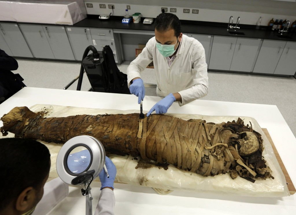 Egyptian conservators clean a female mummy dating back to the Pharaonic period, (712-323 BC), in the Grand Museum near Cairo. AP Photo/Amr Nabil