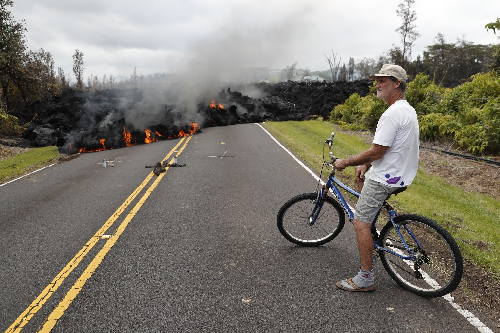 Leilani Estates resident Sam Knox watches the lava stretch across the road, Saturday, May 5, 2018, in Pahoa, Hawaii. Knox's home is less than a few hundred yards from the lava flow and he does not have any plans to evacuate. Knox is hopeful the lava will not take his home. (AP Photo/Marco Garcia)