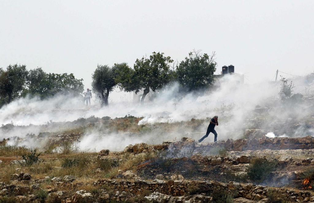 A Palestinian protester runs from tear gas fired by Israeli troops during clashes outside Ofer prison near Ramallah. REUTERS/Ammar Awad