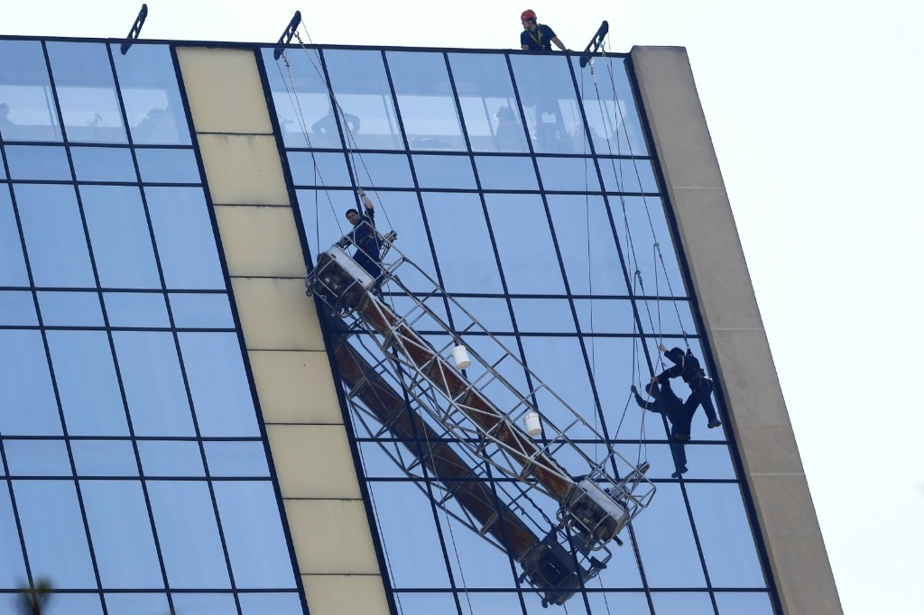Stranded window washers hang on the side of a hotel at downtown Santiago, Chile. Firefighters rescued them. REUTERS/Ivan Alvarado