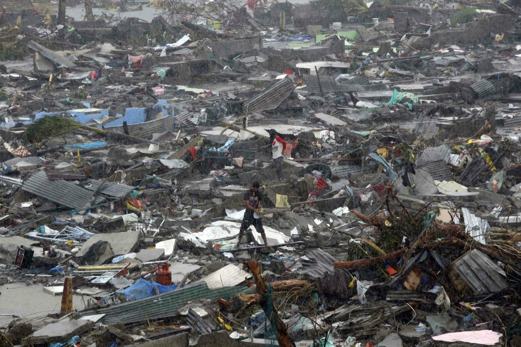 A man stands atop debris as residents salvage belongings from the ruins of their houses. REUTERS/Erik De Castro