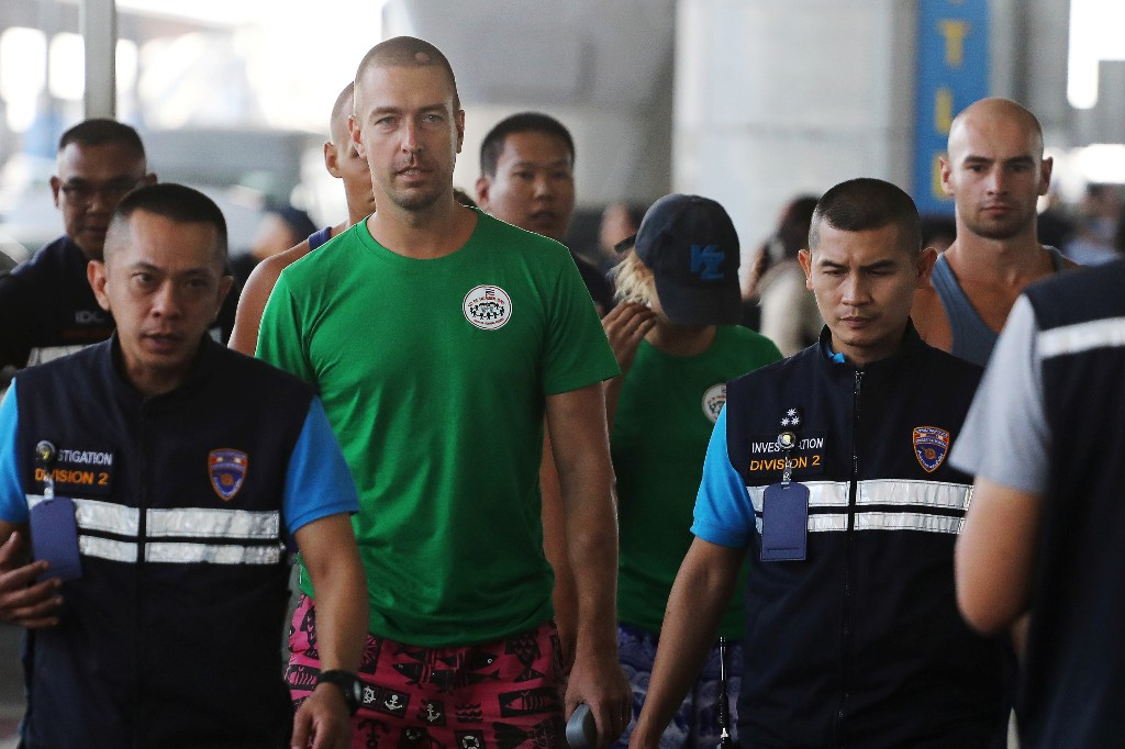 Anastasia Vashukevich (wearing cap), a Belarusian model and escort who caused a stir last year after she was arrested in Thailand and said she had evidence of Russian interference in the 2016 U.S. presidential election, and Alexander Kirillov, a self-described sex coach (2nd L), are pictured before being deported at Bangkok's International airport, Thailand, January 17, 2019. REUTERS/Athit Perawongmetha