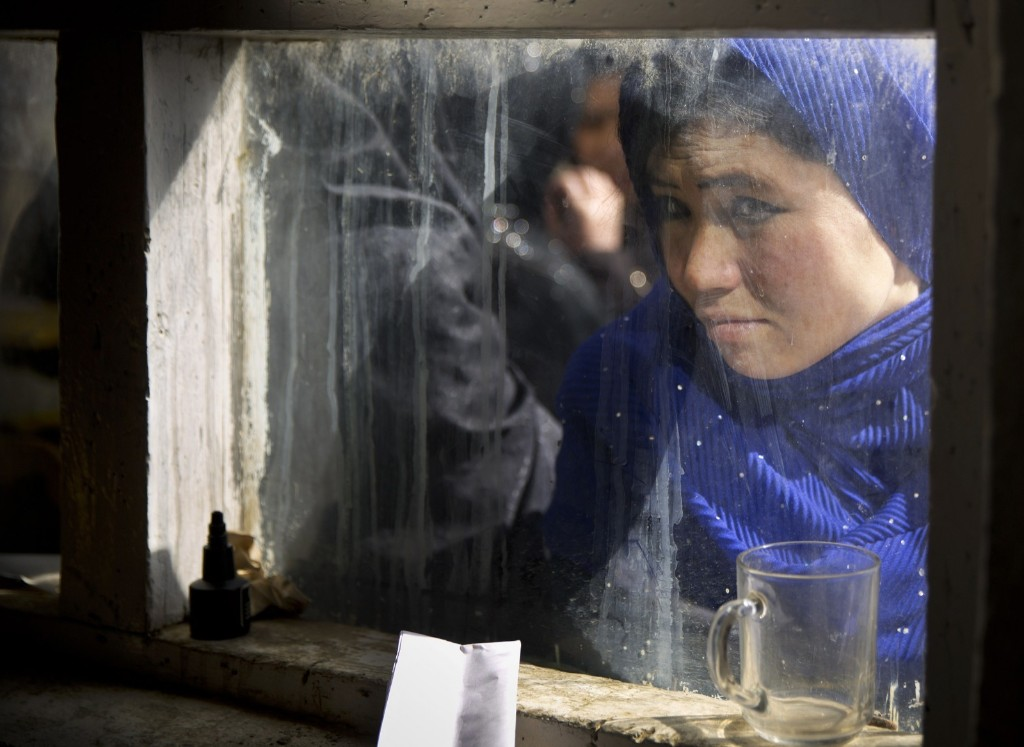 An Afghan woman peers through a window where registration is taking place for the upcoming presidential elections in Kabul. AP Photo/Anja Niedringhaus
