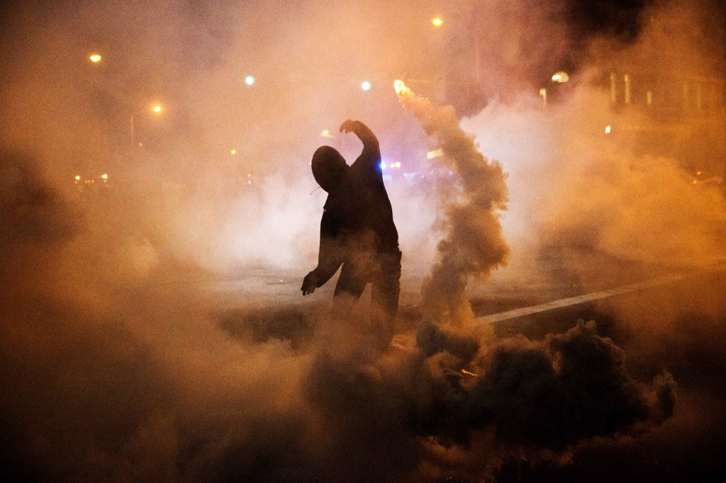 A protester throws a tear gas canister back toward riot police after a 10 p.m. curfew went into effect in the wake of Monday's riots in Baltimore. AP Photo/David Goldman